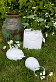 Sprigs of jasmine in white vases and old canister next to floor vase in garden
