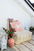 Floor cushion with embroidered scatter cushions on sequinned rug, Moroccan ceramic vase and lanterns as Oriental decorations on modern roof terrace