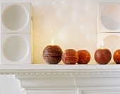 Lit sphere candles on mantelpiece