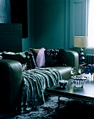Velvet throw draped over green leather sofa in contemporary sitting room