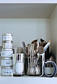 Close up of shelf with silver cutlery and containers