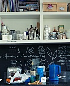 Items stored on open shelving unit in contemporary kitchen with chalkboard