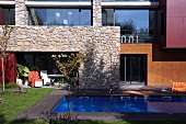 Swimming pool in garden of modern house with stone wall