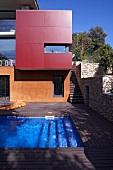Moderne Architektur mit farbigen und gläsernen Fronten und einer Holzterrasse mit Swimmingpool