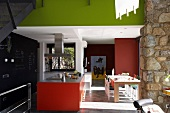 Modern kitchen with colourful red and spring green surfaces in open-plan interior