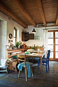 Rustic kitchen with wooden ceiling, dining table, wooden chairs and corner bench