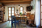 Rustic kitchen with wooden ceiling, dining table, wooden chairs & corner bench
