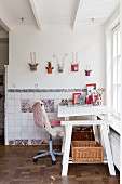 White adjustable desk and sheepskin on desk chair below creative wall decorations and hand-made traditional wall tiles