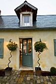 Simple, country house in northern France with slate roof, pointed dormer and unusual planting on either side of front door