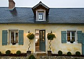 Simple, country house in northern France with slate roof, pointed dormer and elegant planting on either side of front door