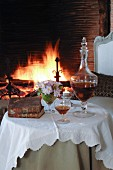 Nostalgisch gedeckter, runder Tisch mit Portweinkaraffe und Weinglas vor brennendem Kaminfeuer