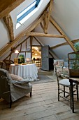 Simple attic room with rustic wooden floor, exposed, old roof beam structure and skylight