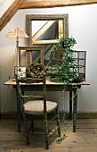 Rustikaler Holztisch mit Antiquitäten; davor ein Vintage-Stuhl