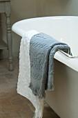 Graues und weisses Handtuch über dem Badewannenrand einer freistehenden Badewanne hängend