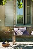 Kissen auf Holzbank, zierlicher Bistrotisch und Korb mit Lavendelstrauss vor dem Fenster eines provenzalischen Landhauses