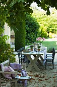 Set, rustic table and small bench with scatter cushions on gravel terrace in Mediterranean garden
