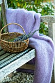 Fluffy, lilac blanket and basket of lavender on bench in garden