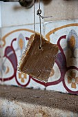 Natural soap on a rope hanging in front of tiles with original pattern in kitchen of house in southern France