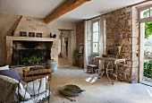 Interior in restored country house with soot-blackened fireplace and delicate, French metal furniture against stone walls