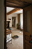 View through open door into interior of restored country house with rustic stone floor in southern France