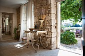 Delicate, old metal table against rustic stone wall and view of garden through open door