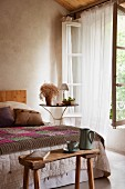 Wooden bench at foot of bed with counterpane; airy curtains at open window to one side