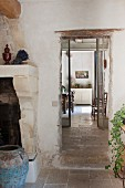 View past masonry fireplace and blue floor vase into Proven