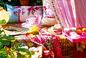 Colourful throws on bench, flip-flops, teacup and cushions in garden