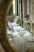 Reflection of dining table with elegant place settings and gilt, Baroque chairs