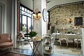 Weitläufiger Wohnraum mit gläsernem Erker, rustikalen Wänden und edlem Mobiliar