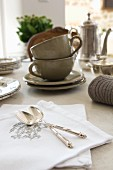 Silver spoons on white, embroidered damask napkins