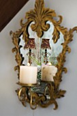 Lit candle in ornate, mirrored candle sconce with gilt frame