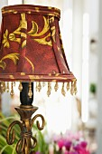 Table lamp with red and gold lampshade and beaded trim