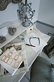 Pretty table lamp on white bureau against grey wall