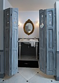 Antique sink below oval, gilt-framed mirror; grey, folding panelled door in foreground