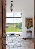 View into living area of detached house with rustic stone floor and large panoramic windows