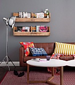 Home-made, wall-mounted rustic shelves above modern leather sofa with colourful cushions