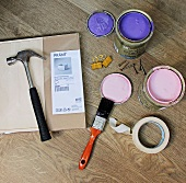 Paint pots, masking tape and tools next to a storage box still in its package