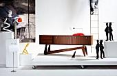 Designer table and designer lamp on pedestals; sideboard and designer tables with sculptural elements on platform