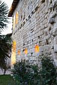 Illuminated window apertures in facade of Chateau Maignaut