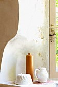 Still-life of cake mould, earthenware bottle and jug in curved window niche