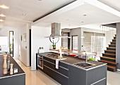 Freistehende Küchentheke mit grauen Oberflächen unter abgehängter Decke in modernem, offenem Wohnraum gegenüber Treppenaufgang