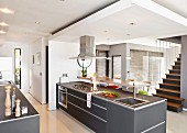 Free standing, gray kitchen counter under a suspended ceiling in a modern, open living room with stairs