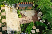 View down onto precise garden with stone-floored seating area, rows of flower pots and beds between stone flags