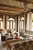 Moroccan-style living room with wood-beamed ceiling, arched windows and comfortable sofa combination
