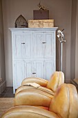 Shabby chic wardrobe behind tasteful leather armchairs