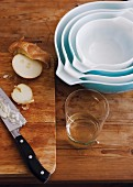 Set of baking dishes on wooden table next to sliced onion on chopping board