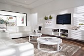 White living room with white leather sofa set and circular coffee table on flokati-style rug; flat screen TV above sideboard