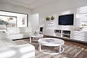 Weisses Wohnzimmer mit weisser Ledersofagarnitur und kreisförmige Couchtische auf flokatiartigem Teppich vor Sideboard unter Flachbild-Fernseher