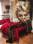 Black metal bed with claret bed linen and fur blanket; large portrait of Marilyn Monroe on wall